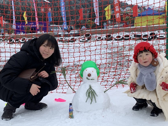 2游客与亲手堆成的雪人合影。华龙网-新重庆客户端 陶彦燕 摄