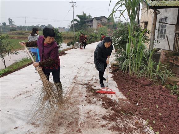 华兴镇茯苓村女社长陈昌琼(右)带领村民一起清扫公路 特约通约员 谢凤 摄