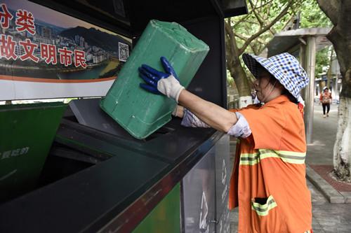 保洁员按照分类要求投放垃圾。特约通讯员 隆太良 摄